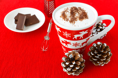 Hot Chocolate with foamed milk, sprinkled with grated chocolate, in a festive mug with winter motives and a small whisk, chocolate and chocolate grater on red place mat surrounded by snowy pine cones.