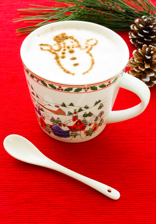 foamed: Hot Chocolate with cinnamon snowman on foamed milk, in a mug with winter motive on festive red background. White porcelain spoon in foreground, pine tree twig and snowy white painted pine cones in background.