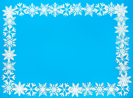 solid blue background: Snowflake Frame out of artificial white snowflakes on solid blue background. Stock Photo