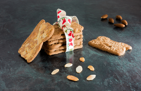 Closeup of a stack of spiced biscuits with almonds ( Spekulatius ) decorated with Christmas Bow, surrounded by almonds on black background.