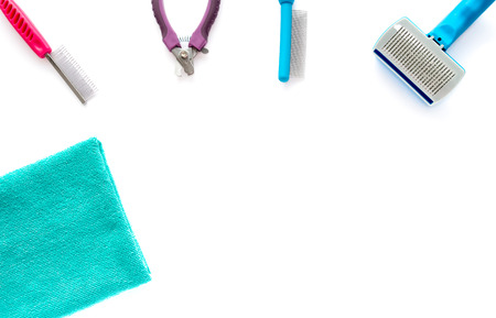 cat grooming: Cat and dog grooming tools: fine toothed comb, wide toothed comb, slicker brush, small nail clipper and a microfiber towel isolated on white background.