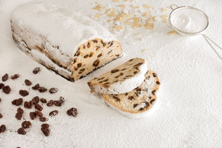 Christstollen with two slices cut off on White Icing Sugar surrounded by almond slivers, raisins and a small stainless steel sieve.