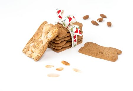 Closeup of a stack of spiced biscuits with almonds ( Spekulatius ) decorated with Christmas Bow, surrounded by almonds and more biscuits on white background. Stock Photo