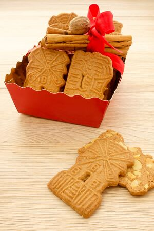 Red tray full of spiced biscuits with almonds, Spekulatius mit Mandeln, decorated with a red Christmas bow, cinnamon sticks, cloves and muscat. Backlit and on light brown wooden background.