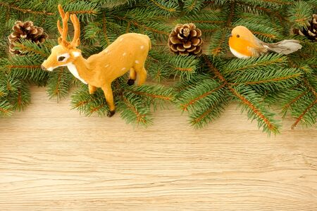 Christmas Scene and Christmas Border with Reindeer, Robin Bird, Pine Cones and Fir Tree Twigs on light brown wooden background with copy space. Stock Photo