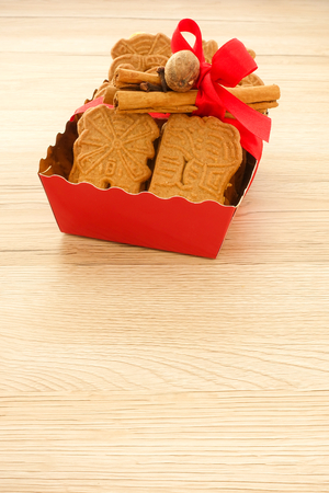 Red tray full of spiced biscuits with almonds, Spekulatius mit Mandeln, decorated with a red Christmas bow, cinnamon sticks, cloves and muscat. Backlit, light brown wooden background and lots of copy space. Stock Photo