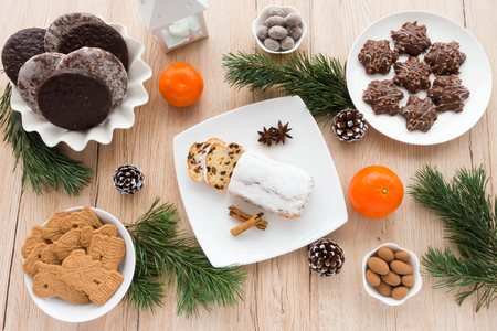Arrangement of Gingerbread, Spiced Biscuits and Mini Christstollen on light wooden background surrounded by Christmas decoration.
