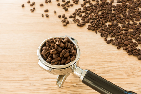 energizing: Portafilter, filter holder, of a professional espresso machine filled with freshly roasted coffee beans. In the background coffee beans spread out on a light brown wooden background. Selective focus, shallow depth of field and backlit.