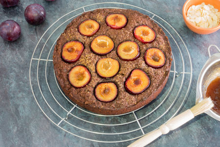 Freshly baked sticky chocolate plum cake on cooling rack surrounded by whole plums, almond slivers in a bowl and heated apricot jam in a bain-marie with pasty brush on the edge.