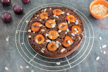 Closeup of a homemade sticky chocolate plum cake on cooling rack, freshly glazed with apricot jam and decorated with almond slivers. In the background fresh plums and almond slivers in a terracotta bowl.