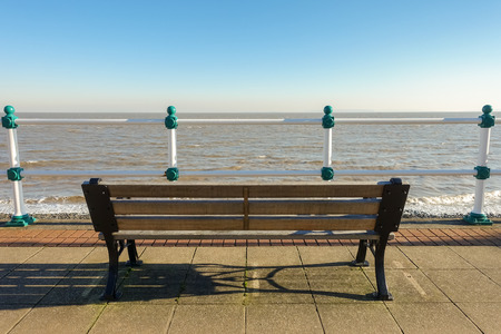 Empty wooden bench on a promenade overlooking the sea on a sunny day in winter. Stock Photo