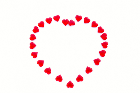 Large heart shaped out of small shiny acrylic red hearts on white background with lots of copy space.
