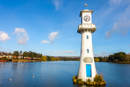 Public Roath Park with Lake, Boat House, Boats and Robert Scott Memorial Lighthouse in Cardiff, Wales, UK. Photo taken in March 2017.