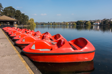 A row of red paddle boats, pedalos for recreation parked at Roath Park Lake, Cardiff, Wales, UK. Stock Photo