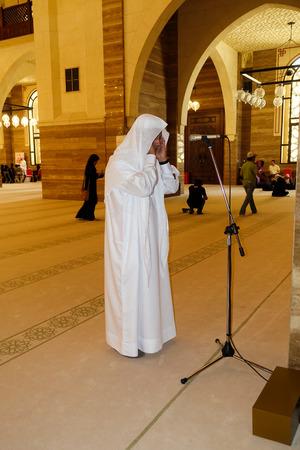 thoub: Manama, Bahrain - July 9, 2016: Arab Muezzin standing in the Al Fateh Grand Mosque leading prayer.