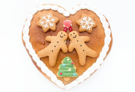 Close up of a cute Gingerbread heart decorated with Gingerbread Men, Gingerbread Stars and a Christmas Tree Cookie on white background.