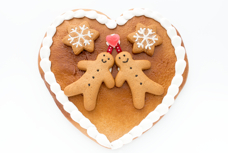 Close up of a cute Gingerbread heart decorated with Gingerbread Men and Gingerbread Stars on white background.