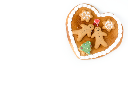 Close up of a cute Gingerbread heart decorated with Gingerbread Men, Gingerbread Stars and a Christmas Tree Cookie on white background with lots of copy space.