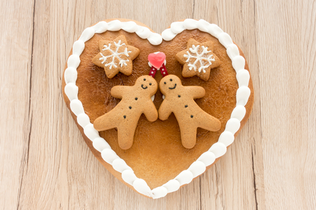 Close up of a cute Gingerbread heart decorated with Gingerbread Men, Gingerbread Stars and a Christmas Tree Cookie on light brown wooden background.