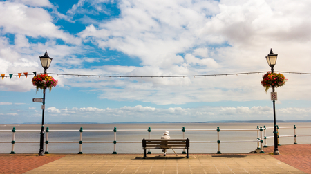 Rear view of a senior woman sitting on a bench on the esplanade in Penarth  looking at the sea.