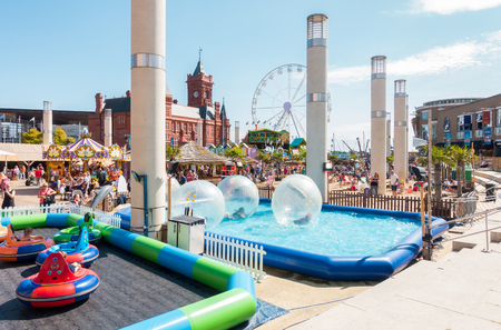 playground rides: Cardiff, United Kingdom -  August 26, 2017: Children and families are enjoying zorb balls, bumper cars and other activities at Cardiff Bay Beach fair at Roald Dahl Plass in Cardiff Bay, Cardiff.