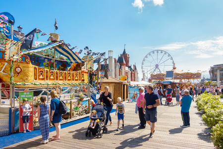 playground rides: Cardiff, United Kingdom -  August 26, 2017: People enjoying themselves on a sunny day at the Cardiff Bay Beach Fair, an urban seaside beach fair at Roald Dahl Plass in Cardiff Bay, Cardiff.