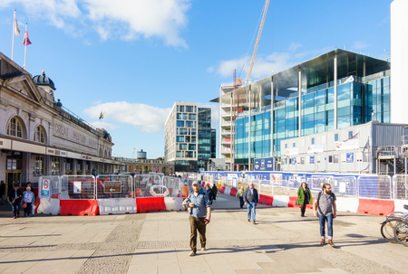 Cardiff, United Kingdom, Wales - October 27, 2017: People are leaving Cardiff Central train station and are passing through the construction site at Central Square, previously the central bus station opposite Cardiff Central train station.