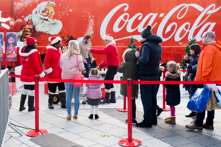 Cardiff, United Kingdom -  November 19, 2017: People are queueing in front of the Coca Cola Christmas truck in Cardiff to have their photos taken by the Coca-Cola stuff. Editorial