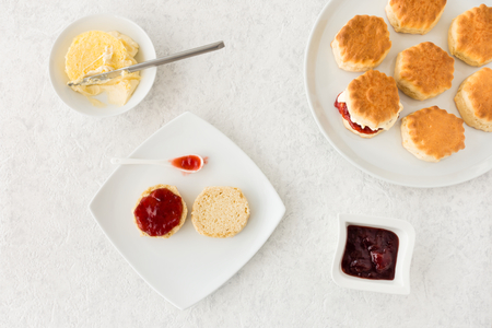 Scones with clotted cream and strawberry jam on white marbled background. Top view.