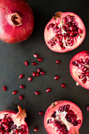 Whole and halved pomegranates with scattered seeds on black background. Top view.