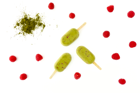 Matcha and Raspberry Popsicles on white background with matcha powder and fresh raspberries.