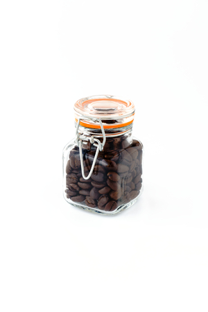 Mini preserving jar with wire clamp closure filled with roasted coffee beans on white background.