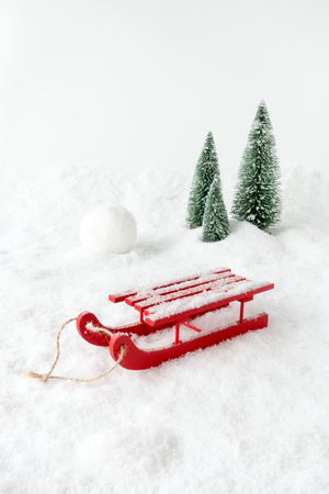 Winter Scene with a red wooden sledge, snow, a giant snowball and fir trees. Imagens
