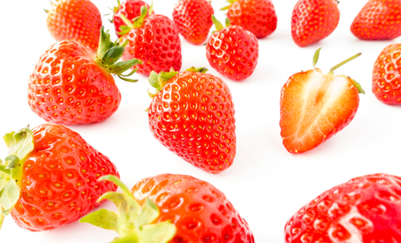 Closeup of fresh, vibrant strawberries with green stems on white background. Imagens - 112529625