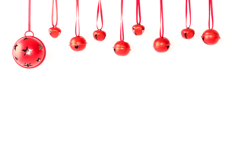 White Christmas jingle bells with red ribbon hanging in front of white background with snowflakes. Stock Photo