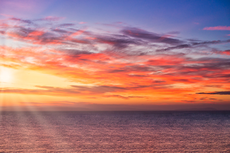 Dramatic sunrise with sun rays over the sea in vibrant yellow, orange, pink and purple colors.