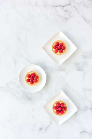 Homemade tartlets filled with fresh raspberries and lemon cream on white porcelain plates and white marble. Top view.