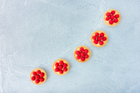 Homemade tartlets filled with fresh raspberries and lemon cream on blue concrete background. Top view. Stock fotó