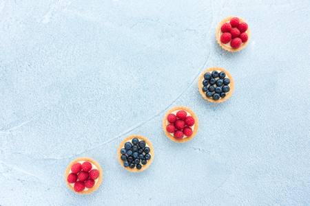 Homemade raspberry and blueberry tartlets with lemon curd cream on blue concrete background. Top view.