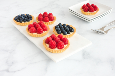 Homemade raspberry and blueberry tarts with a cream filling on white marble board and plates.