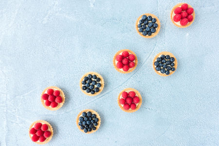 Homemade blueberry and raspberry tartlets with lemon curd cream on blue concrete background. Top view.