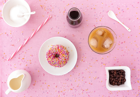 Pink frosted donut with colorful sprinkles, a glass filled with cold brew coffee, cold brew coffee concentrate in a small milk bottle and a straw on pink background with multi colored sprinkles.