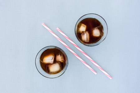 Two straws and two glasses filled with ice coffee and ice cubes on blue background with lots of copy space. Top view.