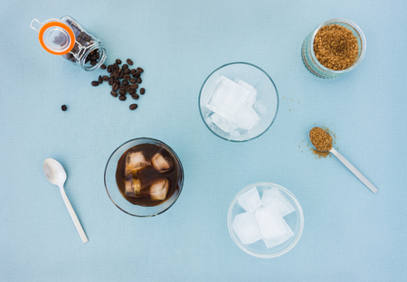 Glasses of cold brew coffee, coffee beans, sugar and a bowl filled with ice cubes on blue background. Top view. Stock fotó