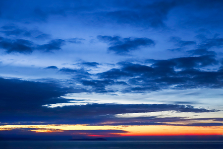 Twilight sky background with dark blue clouds and sunrise in yellow, orange and red colors above the sea. Фото со стока - 115378546