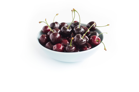 Close-up of a blue bowl filled with fresh cherries isolated on white background. Angled view.