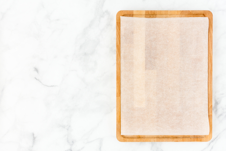 Wooden chopping board with white parchment paper on white marble background with lots of copy space. Top view. Foto de archivo