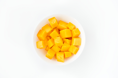 Mango cubes in a white porcelain bowl isolated over white background with lots of copy space. Top view.