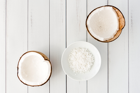 Two coconut halves and coconut flakes in a white porcelain bowl on white wooden background with copy space. Top view.