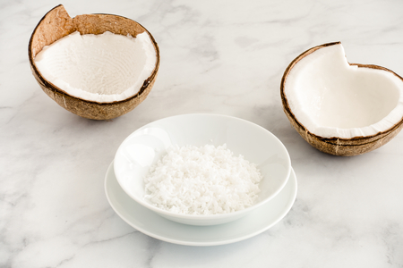 Two coconut halves and coconut flakes in a white porcelain bowl on white marble background with copy space. Angled view.